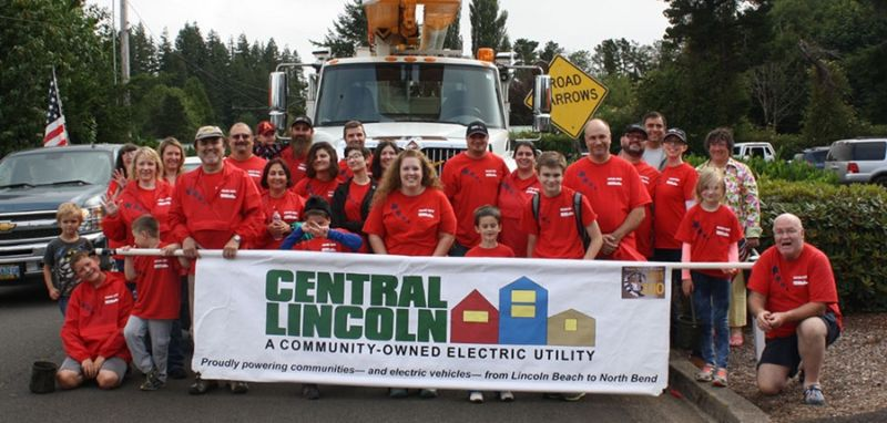 People wearing matching tshirts stand in front a utility trick and hold a banner with the Central Lincoln PUD logo