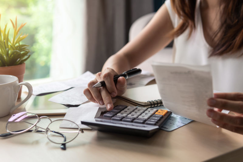 woman looking at document and using calculator