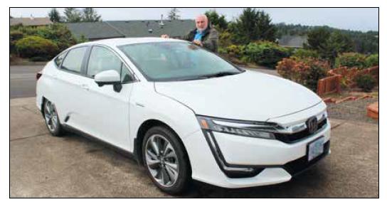 man standing with hands on top of Honda sedan