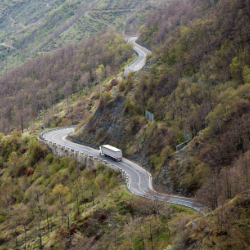 image of a semi truck driving on a long and winding road in the mountains